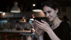 Belle jeune femme s'asseyant en café et à l'aide du smartphone Message de dactylographie femelle attrayant sur l'écran tactile banque de vidéos