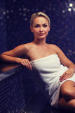 Belle jeune femme s'asseyant en serviette de bain Image stock