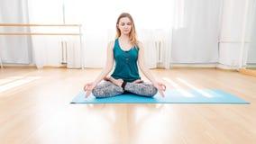 Belle jeune femme s'asseyant sur la position de lotus avec les yeux fermés Photographie stock libre de droits