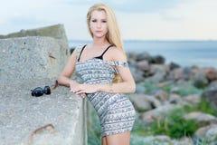 Belle jeune femme s'asseyant sur la roche Photo libre de droits