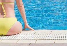 Belle jeune femme s'asseyant sur le bord de la piscine Photographie stock