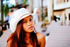 Belle jeune femme s'asseyant sur le lit pliant avec le chapeau sur la station balnéaire, vacances d'été Image libre de droits