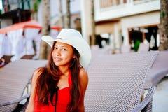 Belle jeune femme s'asseyant sur le lit pliant avec le chapeau sur la station balnéaire, vacances d'été Photos stock