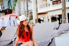 Belle jeune femme s'asseyant sur le lit pliant avec le chapeau sur la station balnéaire, vacances d'été Photo libre de droits