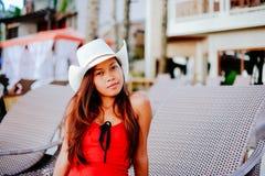 Belle jeune femme s'asseyant sur le lit pliant avec le chapeau sur la station balnéaire, vacances d'été Images libres de droits