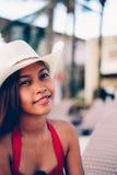 Belle jeune femme s'asseyant sur le lit pliant avec le chapeau sur la station balnéaire, vacances d'été Photographie stock