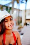 Belle jeune femme s'asseyant sur le lit pliant avec le chapeau sur la station balnéaire, vacances d'été Photos libres de droits
