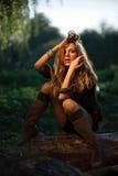Belle jeune femme s'asseyant sur le log photos stock