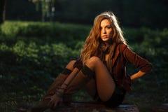 Belle jeune femme s'asseyant sur le log image libre de droits