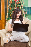 Belle jeune femme s'asseyant sur le sofa avec le smili d'ordinateur portable images stock