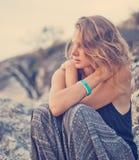 Belle jeune femme s'asseyant sur les roches au coucher du soleil image stock