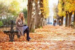 Belle jeune femme s'asseyant sur un banc Photo stock