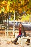 Belle jeune femme s'asseyant sur un banc Photographie stock