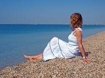Belle jeune femme s'asseyant sur un littoral photos stock