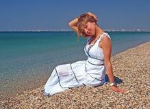 Belle jeune femme s'asseyant sur un littoral image libre de droits