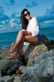 Belle jeune femme s'asseyant sur une roche par l'océan Photos libres de droits