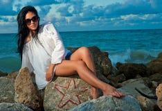 Belle jeune femme s'asseyant sur une roche par l'océan images stock