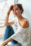 Belle jeune femme sale avec des peintures se reposant près de la fenêtre Image stock