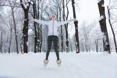 Belle jeune femme sautant la neige en hiver Photo stock