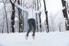 Belle jeune femme sautant la neige en hiver Photos libres de droits