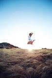 Belle jeune femme sautant sur un pré dans la montagne Photos stock