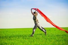 Belle jeune femme sautant sur un pré vert Photo libre de droits