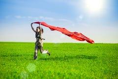 Belle jeune femme sautant sur un pré vert Photo stock