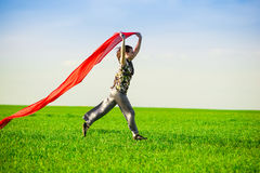 Belle jeune femme sautant sur un pré vert Photos libres de droits