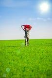 Belle jeune femme sautant sur un pré vert Photographie stock libre de droits