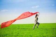 Belle jeune femme sautant sur un pré vert Photographie stock