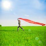 Belle jeune femme sautant sur un pré vert Images stock
