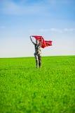 Belle jeune femme sautant sur un pré vert avec le tissu coloré Photographie stock