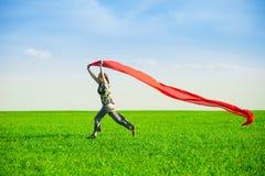 Belle jeune femme sautant sur un pré vert avec le tissu coloré Photographie stock libre de droits