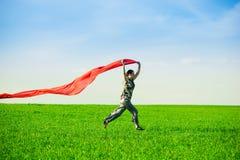 Belle jeune femme sautant sur un pré vert avec le tissu coloré Image libre de droits