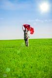 Belle jeune femme sautant sur un pré vert avec le tissu coloré Photo stock