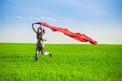 Belle jeune femme sautant sur un pré vert avec le tissu coloré Images stock