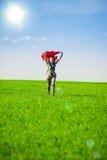 Belle jeune femme sautant sur un pré vert avec le tissu coloré Images libres de droits