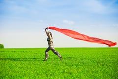 Belle jeune femme sautant sur un pré vert avec le tissu coloré Photos libres de droits