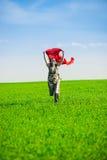 Belle jeune femme sautant sur un pré vert avec le tissu coloré Photos stock
