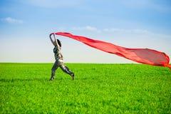 Belle jeune femme sautant sur un pré vert avec le tissu coloré Image stock