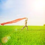 Belle jeune femme sautant sur un pré vert avec un tissu rouge coloré Photographie stock