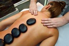 Belle jeune femme se couchant sur le lit de massage images stock