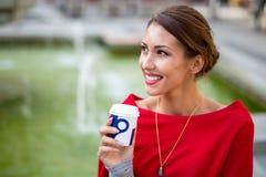 Belle jeune femme se reposant dehors à un puits tout en buvant c photo stock