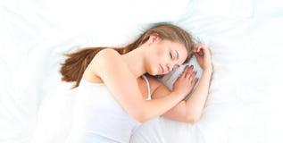 Belle jeune femme se situant dans le lit confortablement et avec bonheur Image stock