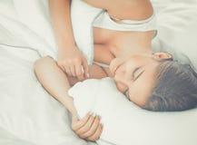 Belle jeune femme se situant dans le lit confortablement et avec bonheur photo stock