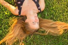Belle jeune femme se situant dans le pré Appréciez la nature photographie stock