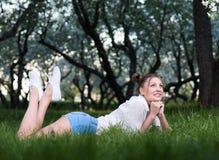 Belle jeune femme se situant en parc sur l'herbe, pensant à quelque chose ou à rêver image libre de droits