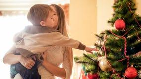 Belle jeune femme se tenant à côté de l'arbre de Noël et embrassant son petit fils photos libres de droits