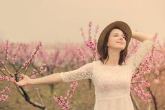 Belle jeune femme se tenant devant le TR de floraison merveilleux Photo stock