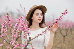 Belle jeune femme se tenant devant le TR de floraison merveilleux Image libre de droits